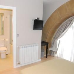 El dormitorio, halógenos empotrados sobre el armario y la pared del fondo empapelada en contraste con el resto de las paredes pintadas. La claridad de las paredes contrasta con el pavimento de nogal.