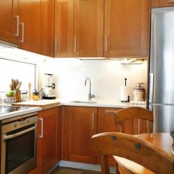 Reforma de cocina, para los muebles se han elegido puertas de madera natural, habituales en las reformas de cocinas, se han colocado los muebles en L y se ha integrado la cocina con el salón buscando un mayor aprovechamiento del espacio y una mayor armonía del conjunto.
