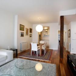 Para esta reforma de vivienda en Donostia San Sebastián realización de una cocina americana integrada con el salón, el poste de amdera visto es una solución habitual en los trabajos de reformas de viviendas