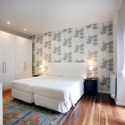 Dormitorio principal, halógenos empotrados sobre el armario y la pared del fondo empapelada en contraste con el resto de las paredes pintadas. La claridad de las paredes contrastan con el pavimento de nogal.