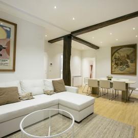 Vista del salón, en primer plano el sofá y al fondo la mesa del comedor y la estructura de madera de la casa.