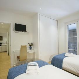 Vista del dormitorio desde el cabecero de la cama, con la mesa de escritorio y el armario al fondo.