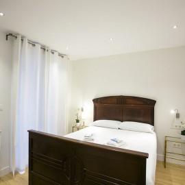 El dormitorio visto desde el pasillo, con las mesillas al fondo y la ventana a la izquierda.