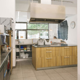 La zona de trabajo con la cocina al fondo, a la izquierda el mobiliario industrial, al fondo la zona de atención al público.