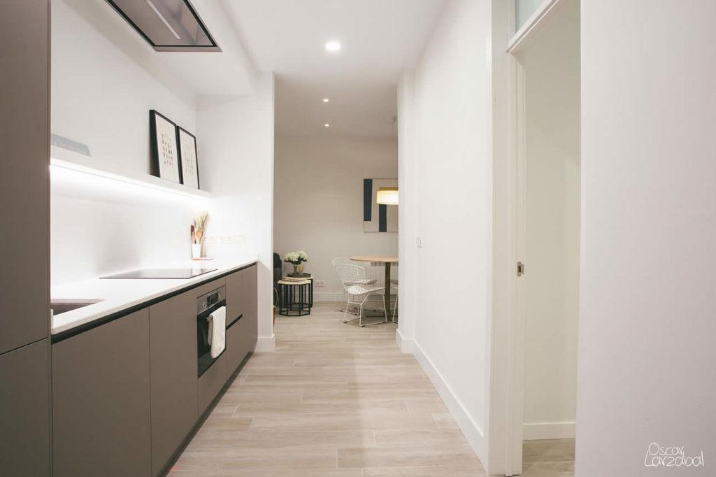Vista de la cocina con el salón al fondo, a la izquierda la balda de Pladur que en su parte inferior tiene iluminación de led. Para los muebles de cocina se ha elegido un tono gris oscuro que combine con el color blanco de la pared y el suelo de gres.