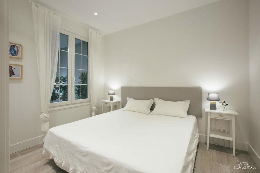 El dormitorio visto desde la entrada, a ambos lados de la cama las mesillas con sus correspondientes lámparas.