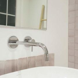 Detalle del grifo empotrado del baño, con un frente de gres para el lavabo, al fondo la ducha.