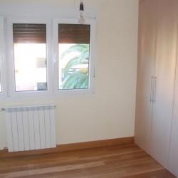 El dormitorio principal visto desde la cama, halógenos empotrados sobre el armario y la pared del fondo empapelada en contraste con el resto de las paredes pintadas. La claridad de las paredes contrasta con el pavimento de nogal. Una de las paredes se ha empapelado.