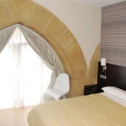Dormitorio principal, halógenos empotrados sobre el armario y la pared del fondo empapelada en contraste con el resto de las paredes pintadas. La claridad de las paredes contrasta con el pavimento de nogal.