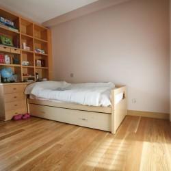 El dormitorio niñas, halógenos empotrados sobre el armario, pared del fondo empapelada en contraste con el resto de las paredes pintadas. La claridad de las paredes contrastan con el pavimento de roble.