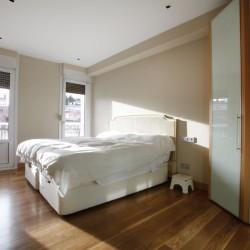 El dormitorio principal visto desde la entrada, halógenos empotrados sobre el armario y la pared del fondo empapelada en contraste con el resto de las paredes pintadas. La claridad de las paredes contrastan con el pavimento de nogal. Una de las paredes se ha empapelado.