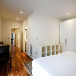 Halógenos empotrados sobre el armario y la pared del fondo empapelada en contraste con el resto de las paredes pintadas. La claridad de las paredes contrastan con el pavimento de nogal.