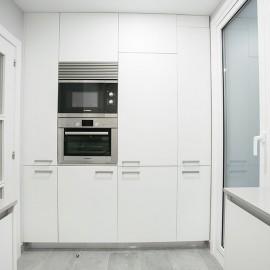 Frente de cocina en el cual se pueden ver el horno y micro hondas empotrados con el resto de los muebles.