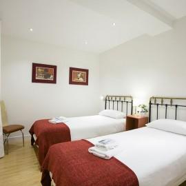 El dormitorio principal visto desde el vestíbulo, pueden verse los focos de led empotrados. La claridad de las paredes contrasta con el pavimento de madera.