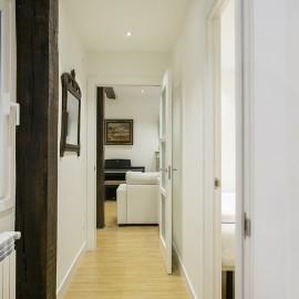 El pasillo con el salón al fondo, en primer plano un poste al que se le ha dejado la madera vista.