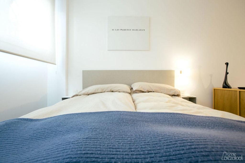 Vista de la cama, para la pintura se ha elegido un tono blanco que combine con la madera de los muebles y los tonos azules del sofá y la cama. El pavimento de gres imitación roble aporta calidez al salón.