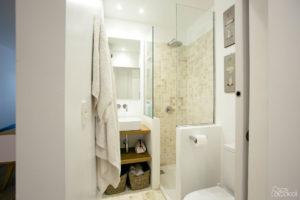 En el baño se ha utilizado una combinación de revestimiento de gresite en las paredes de la ducha y suelo, pintando el resto de las paredes, el lavabo se ha colocado sobre una balda de madera.