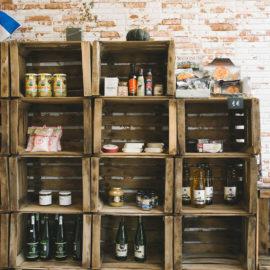 Detalle de las cajas de almacenaje con distintos productos, la pared trasera con revestimiento de gres.
