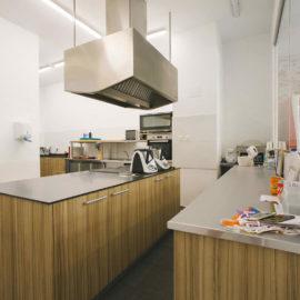 La zona de trabajo con la cocina en primer plano con el mobiliario industrial. Para el suelo se ha elegido pavimento de gres.