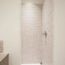 Detalle del baño con la ducha al fondo y a la izquierda el mueble del lavabo.
